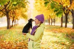 Adolescente sonriente que se relaja con el perro muchacha que juega con un pequeño perro al aire libre en otoño Fotos de archivo libres de regalías