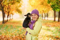 Adolescente sonriente que se relaja con el perro muchacha que juega con un pequeño perro al aire libre en otoño Imágenes de archivo libres de regalías