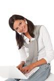Adolescente sonriente que se sienta con la computadora portátil Imágenes de archivo libres de regalías