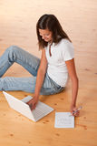 Adolescente sonriente que se sienta con la computadora portátil Fotos de archivo libres de regalías