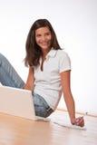 Adolescente sonriente que se sienta con la computadora portátil Fotografía de archivo libre de regalías