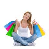 Adolescente sonriente que se sienta con los bolsos de compras Imagen de archivo libre de regalías