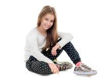 Adolescente sonriente que se sienta en el suelo Imágenes de archivo libres de regalías