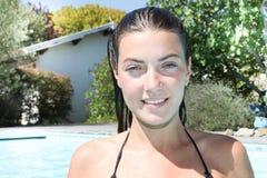 Adolescente sonriente que se sienta en piscina cerca de hogar Foto de archivo libre de regalías