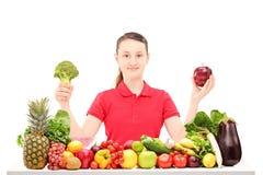 Adolescente sonriente que sienta y que sostiene la manzana y el bróculi Foto de archivo libre de regalías
