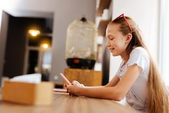 Adolescente sonriente que siente relajado mientras que se sienta en café Foto de archivo