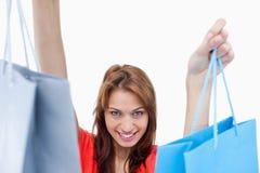 Adolescente sonriente que sostiene bolsos de compras Fotografía de archivo libre de regalías