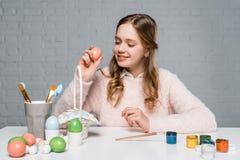 Adolescente sonriente que sostiene el huevo durante la preparación para pascua Fotografía de archivo