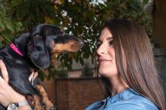 Adolescente sonriente que sostiene el perro basset negro en la mano imagen de archivo