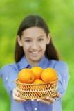 Adolescente sonriente que sostiene la cesta de naranjas Foto de archivo