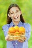 Adolescente sonriente que sostiene la cesta de naranjas Imagen de archivo