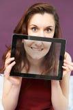 Adolescente sonriente que sostiene la tableta de Digitaces en Front Of Face Foto de archivo