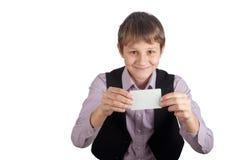 Adolescente sonriente que sostiene la tarjeta blanca vacía en manos Aislado en blanco Imagenes de archivo