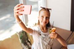 Adolescente sonriente que sostiene su teléfono en cubierta rosada Imagenes de archivo