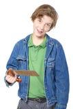 Adolescente sonriente que sostiene una sierra en una mano, aislada en blanco Fotos de archivo libres de regalías