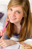 Adolescente sonriente que sueña despierto sobre su diario Imágenes de archivo libres de regalías