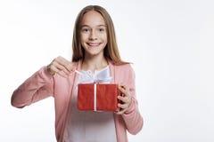Adolescente sonriente que tira de la secuencia en la caja de regalo Imágenes de archivo libres de regalías