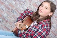 Adolescente sonriente que toca la guitarra Imagen de archivo libre de regalías