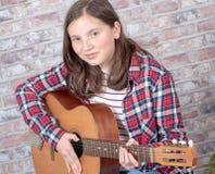 Adolescente sonriente que toca la guitarra Foto de archivo libre de regalías
