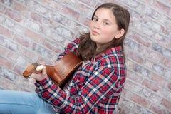 Adolescente sonriente que toca la guitarra Fotos de archivo libres de regalías