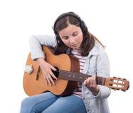 Adolescente sonriente que toca la guitarra en el fondo blanco Imagen de archivo