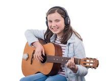 Adolescente sonriente que toca la guitarra en el fondo blanco Imagen de archivo libre de regalías