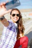 Adolescente sonriente que toma la imagen con smartphone Foto de archivo libre de regalías