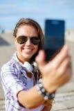 Adolescente sonriente que toma la imagen con smartphone Fotografía de archivo
