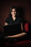 Adolescente sonriente que trabaja en su ordenador portátil Imagen de archivo libre de regalías