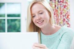 Adolescente sonriente que usa el ordenador en casa Fotos de archivo