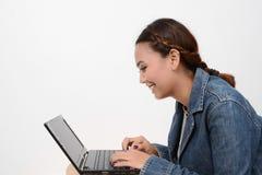 Adolescente sonriente que usa el ordenador portátil Imagen de archivo libre de regalías