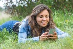 Adolescente sonriente que usa el teléfono elegante al aire libre Foto de archivo