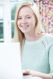 Adolescente sonriente que usa la computadora portátil en casa Foto de archivo libre de regalías