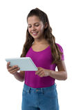 Adolescente sonriente que usa la tableta digital Imagenes de archivo