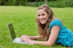 Adolescente sonriente que usa su computadora portátil mientras que se acuesta Foto de archivo libre de regalías