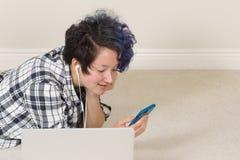 Adolescente sonriente que usa su teléfono celular y escuchando la música Imagen de archivo