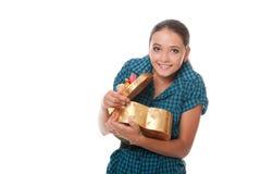 Adolescente sonriente sorprendido con el regalo a disposición Fotografía de archivo