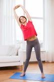 Adolescente sonriente streching en casa Foto de archivo