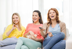 Adolescente sonriente tres que ve la TV en casa Fotografía de archivo