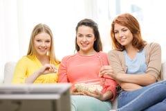 Adolescente sonriente tres que ve la TV en casa Imagenes de archivo
