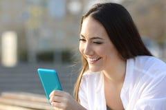 Adolescente sonriente usando un teléfono elegante azul en la calle Foto de archivo