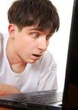 Adolescente sorprendida con el ordenador portátil Fotografía de archivo libre de regalías