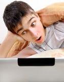Adolescente sorprendido con el ordenador portátil Fotografía de archivo libre de regalías