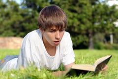 Adolescente sorprendido con un libro Imagen de archivo libre de regalías