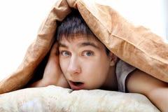 Adolescente sorprendido debajo de la manta Imagen de archivo