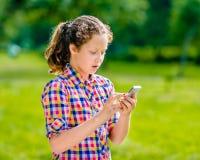 Adolescente sorprendido en ropa casual con smartphone Fotografía de archivo