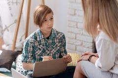 Adolescente sorprendido que visita a su psicólogo de la escuela Foto de archivo libre de regalías