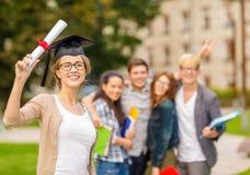 Adolescente sorridente in angolo-cappuccio con il diploma Immagine Stock
