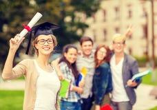 Adolescente sorridente in angolo-cappuccio con il diploma Immagine Stock Libera da Diritti