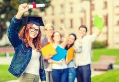 Adolescente sorridente in angolo-cappuccio con il diploma Immagini Stock Libere da Diritti